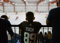 A boy in the stands wears an Alex Tuch jersey watching the Alex Tuch 3 on 3 Pro Hockey Game to benefit Maureen's Hope Foundation.
