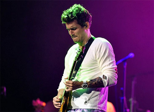 Singer John Mayer, bathed in green and purple stage lights, plays guitar during his concert while wearing a Bead of Courage for Maureen?s Hope Foundation.