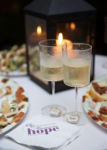 Wine glasses on a candle lit table at the 100 Women with $100 fundraising event for Maureen's Hope Foundation.